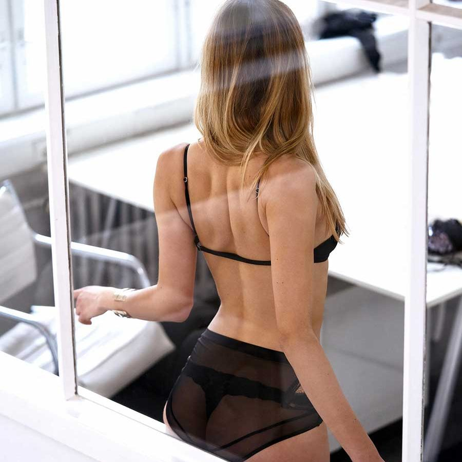 An image of an escort with her ass pressed against the glass sitting on a window frame