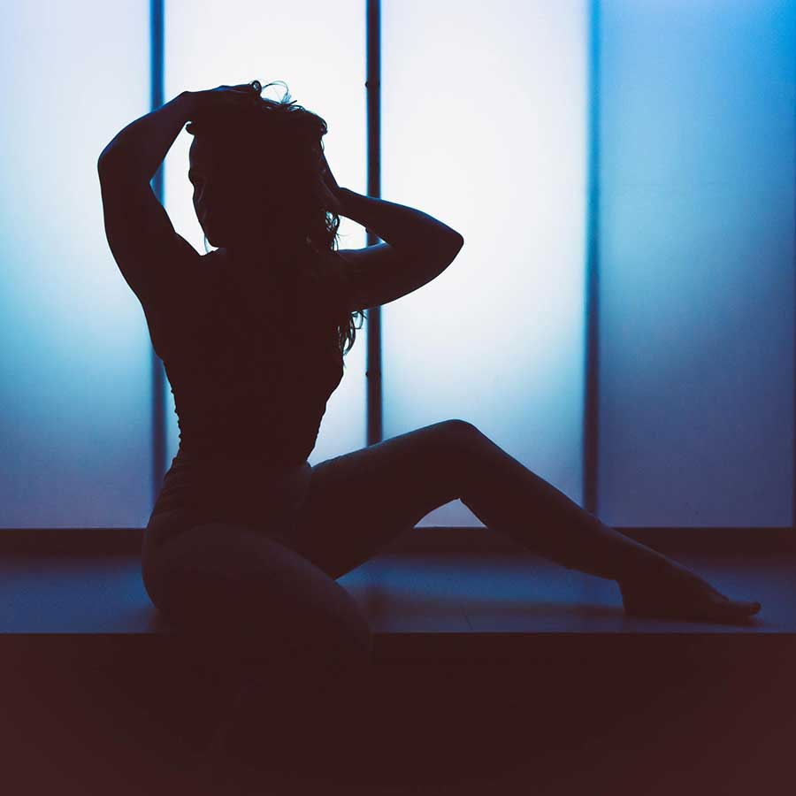a picture of a sexy escort sitting on a counter in front of a darkened window