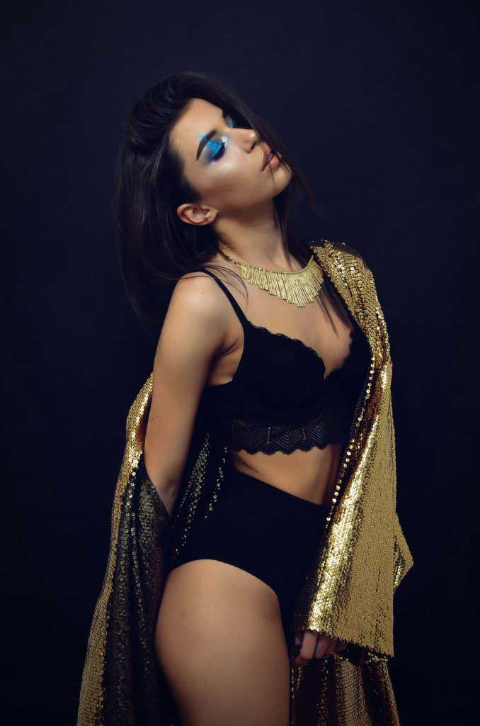 Sydney escort poses in a gold sequinned blanket