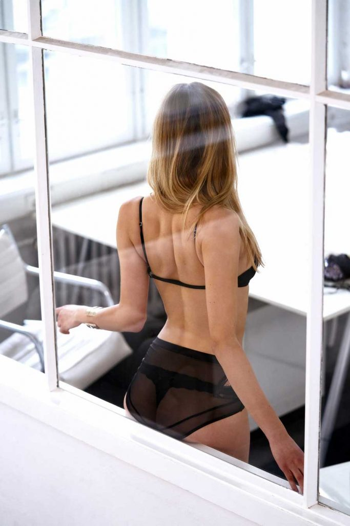 image of a sydney escort with her ass on the window sill