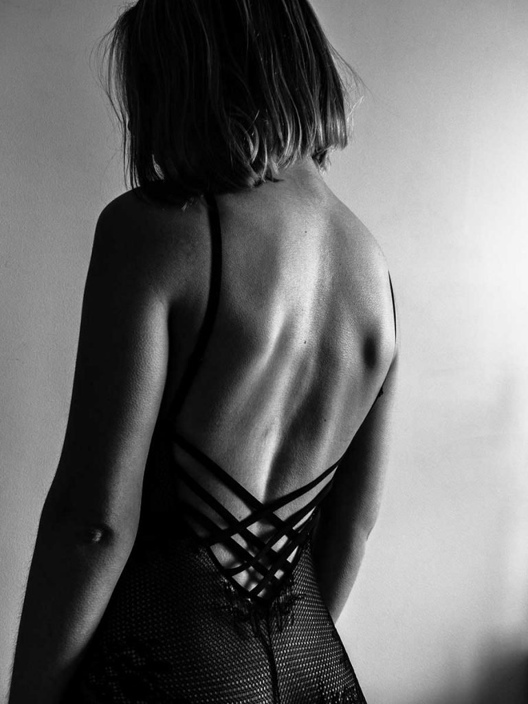 a black and white picture of an escort showing off he back in a sexy dress