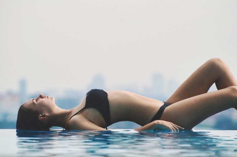Lady in black lingerie lies on water